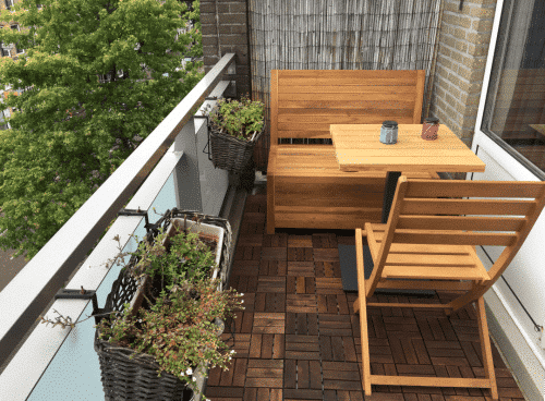 If you have some more space; combine the balcony bench with other wooden furniture.