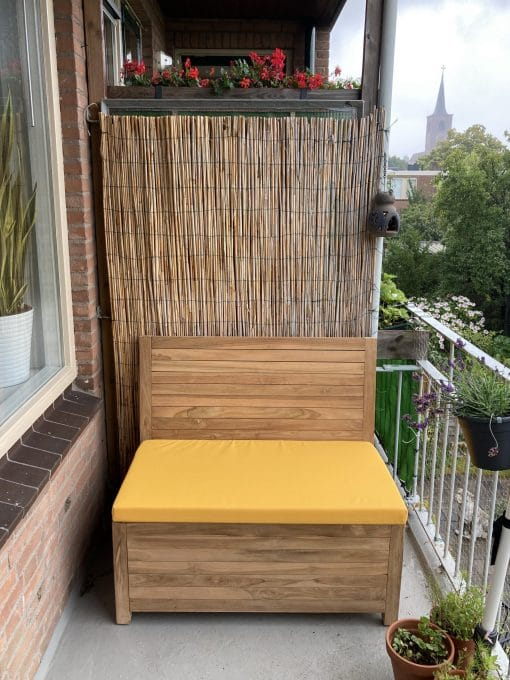 Small wooden balcony bench with a yellow lounge cushion.