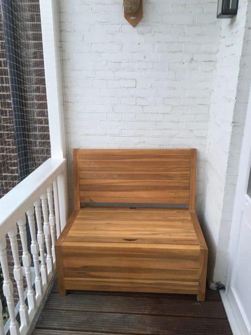 De kleine houten balkon bank doet het goed met een witte balkonmuur.