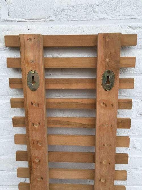 Hang the teak plant wall rack on the wall with two screws that fit in the back.