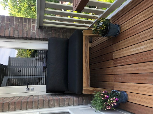Lounge balcony chair made of beautiful dark teak wood on a small and narrow balcony in Amsterdam