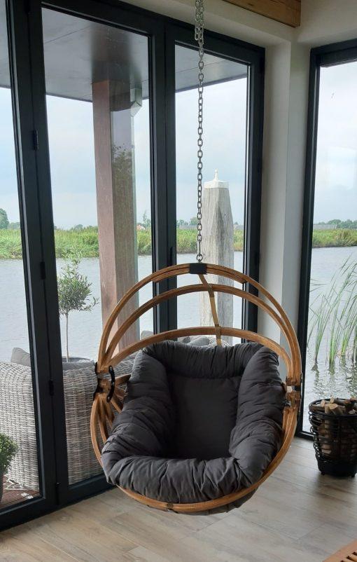 Houten hangstoel ei met dralon kussen aan het water ergens in Friesland