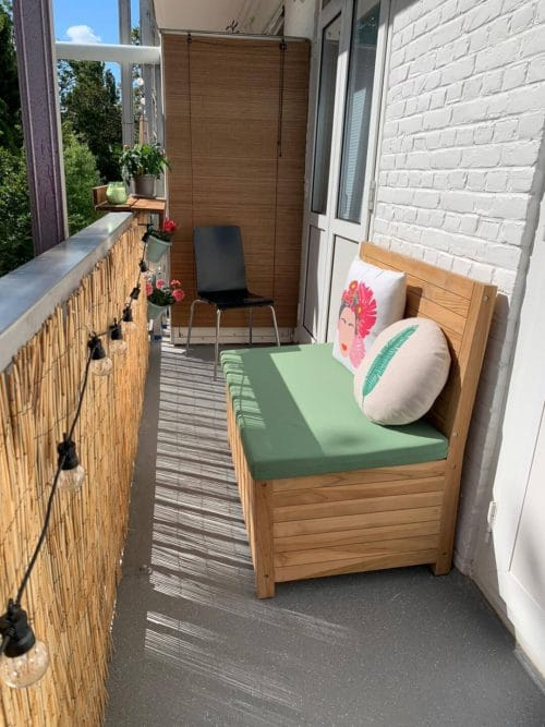 Balcony bench with storage space and a spring green cushion. In combination with the Lumisky Solar Party Lights